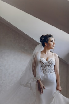 A young and beautiful bride at home standing near window