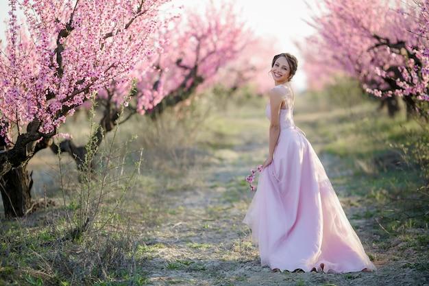 Молодая красивая невеста в цветущем саду.
