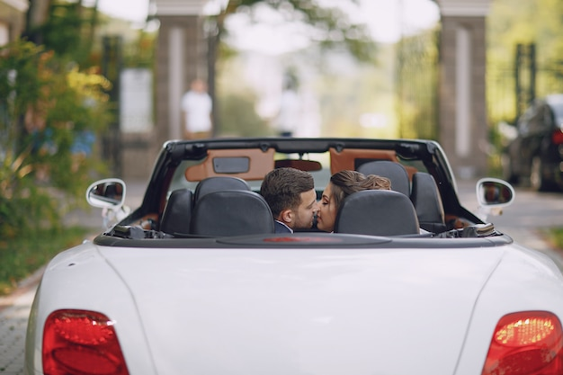 A young and beautiful bride is sitting in a car with her husband