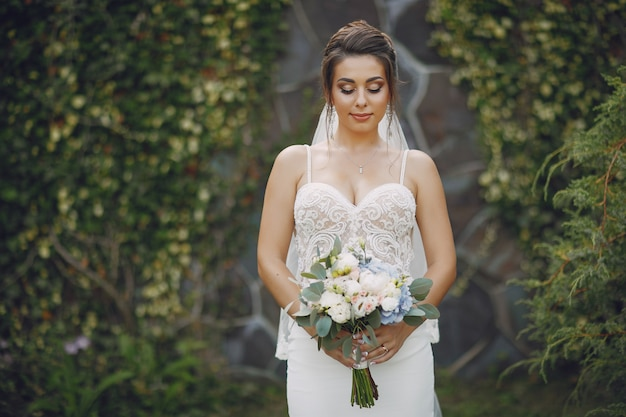 A young and beautiful bride is standing in a summer park with bouquet of flowers