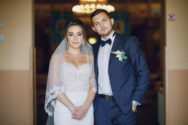 A young and beautiful bride is standing with her husband in a church