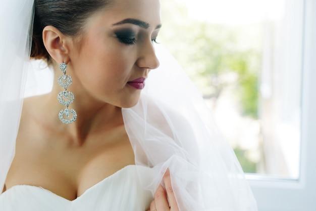 ホテルの部屋の窓に向かってポーズをとって若い美しい花嫁
