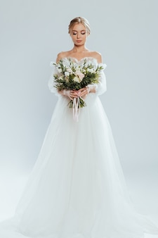 Young beautiful bride posing in wedding dress with bouquet roses