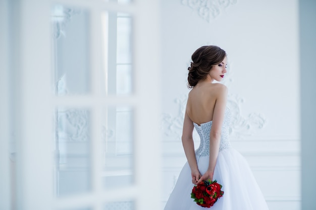 Young beautiful bride standing in antique interior