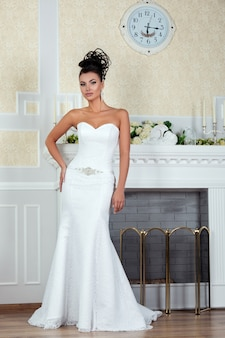 豪華なウェディングドレスで暖炉のそばに立っている若い美しい花嫁