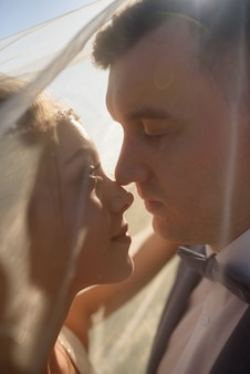 Young beautiful bride take shelter under a photo. bright backlight shines in the frame