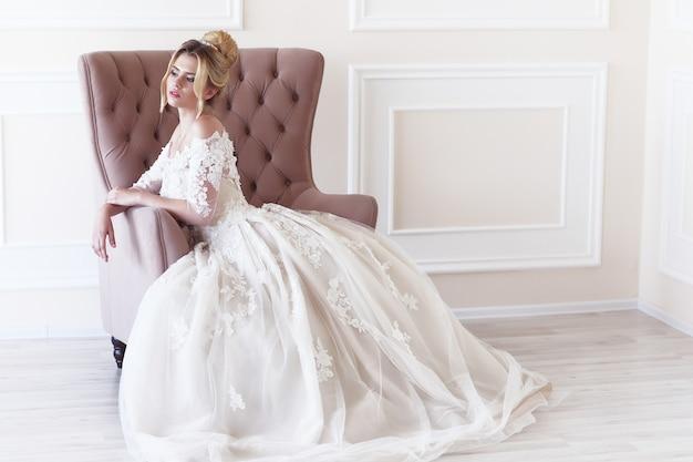 若い美しい花嫁。結婚式のヘアスタイル、ブロンドの髪、ウェディングドレス、メイクアップ、花嫁のブーケ。屋内ショット