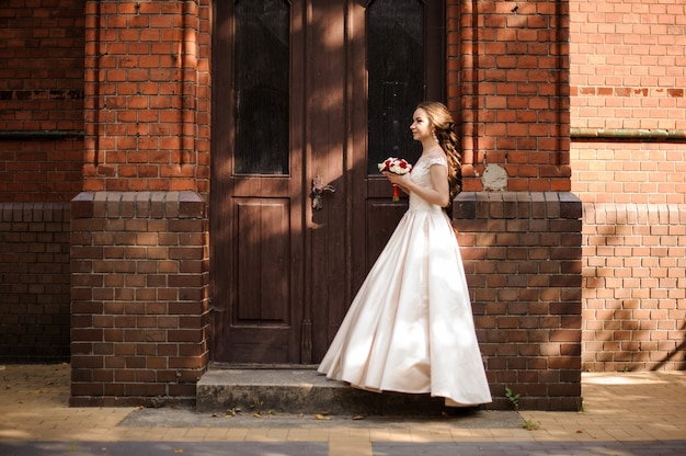Young and beautiful bride in white wedding dress standing near the wooden door of vintage building