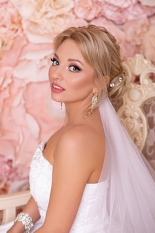 Young beautiful bride with blonde wedding hairstyle and pink flowers background