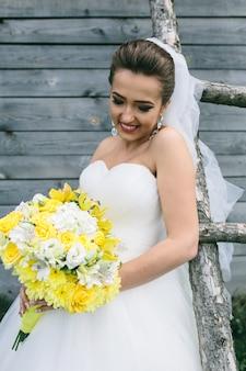 花束を持った若い美しい花嫁がはしごに立っています