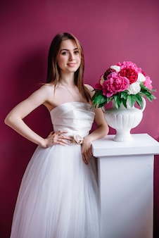 Young beautiful bride with a bouquet of pink peony near the wall