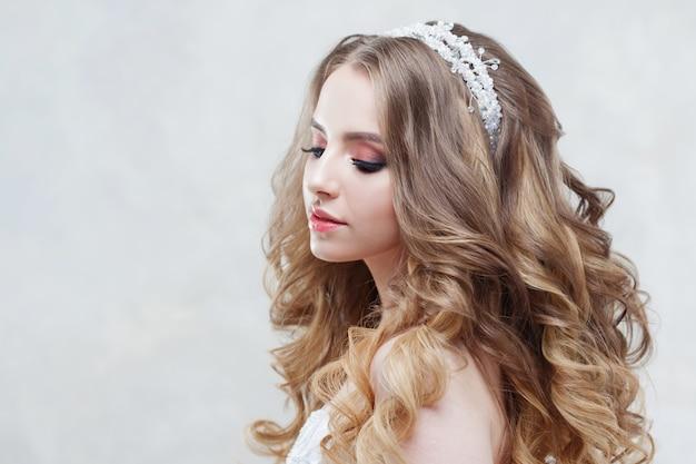 豪華なカールを持つ若い美しい花嫁。ティアラと結婚式のヘアスタイル。