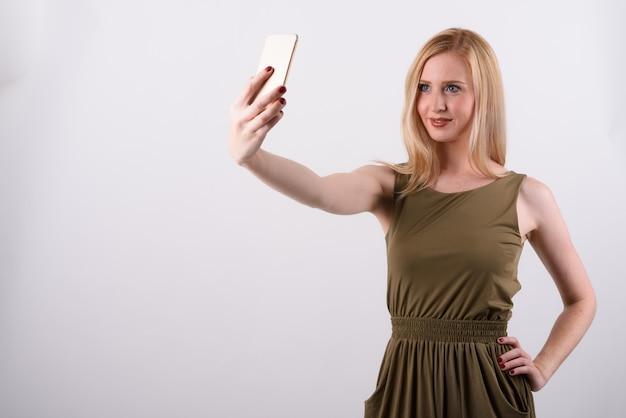 白い背景のブロンドの髪を持つ若い美しいイギリスの女性