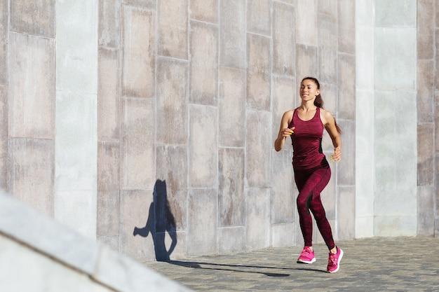 若い美しい茶色の髪の少女は、路上で朝のジョギングに従事しています