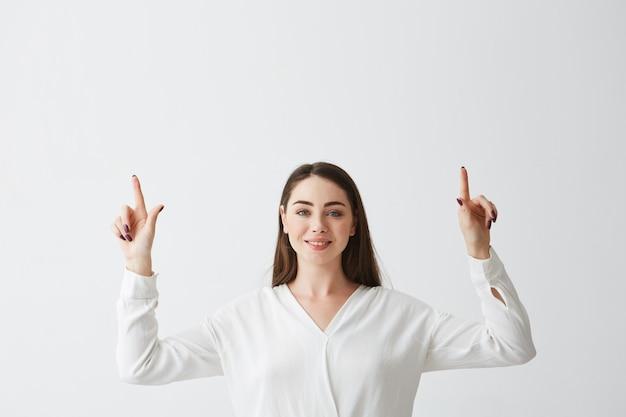 ポインティング指を笑って若い美しいブルネット実業家。