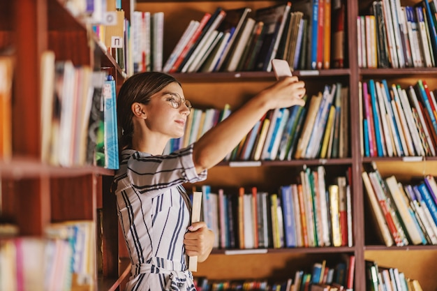 Young beautiful brunette in dress and with eyeglasses holding a book and taking selfie while standing in library.
