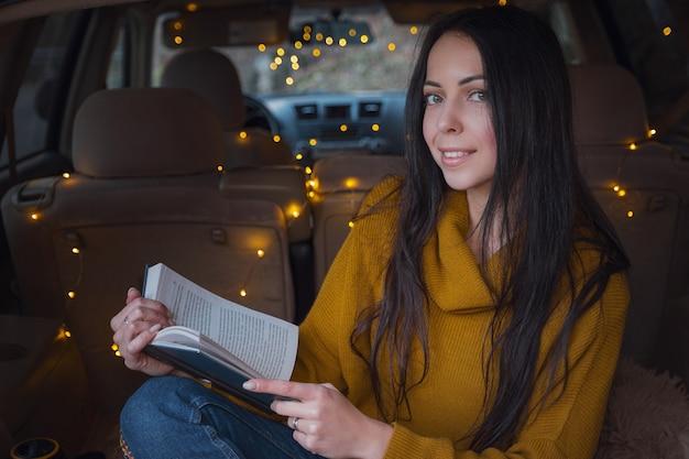 젊은 아름 다운 갈색 머리는 그녀의 차 트렁크에서 휴식을 즐깁니다. 노란 화환과 베이지색 체크무늬가 아늑함을 더하고, 책을 읽고 따뜻한 차를 마시는 여자