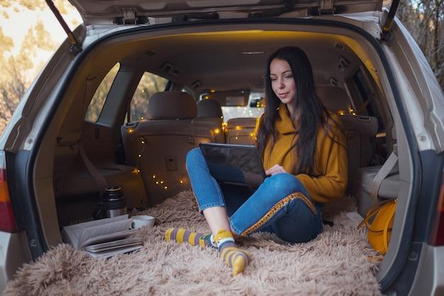 젊은 아름 다운 갈색 머리는 그녀의 차 트렁크에서 휴식을 즐깁니다. 노란색 화환과 베이지색 격자 무늬가 아늑함을 더하고, 이메일을 읽는 여성, 메신저로 채팅하고 노트북으로 화상 회의를 하는 여성
