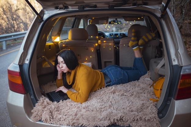 Молодая красивая брюнетка наслаждается отдыхом в багажнике своей машины. желтая гирлянда и бежевый плед создают уют, женщина читает электронную почту, общается в мессенджерах и разговаривает по видеоконференции на ноутбуке