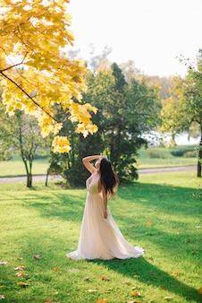 가 공원에서 길고 흰 드레스에 젊은 아름 다운 갈색 머리 여자.