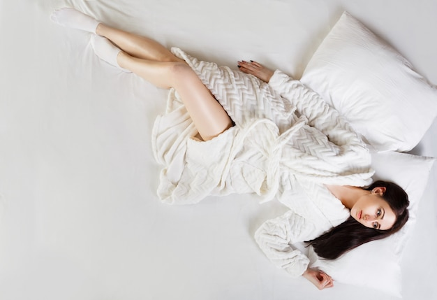 Young beautiful brunette girl in bathrobe lying on bed early in morning. shot from above