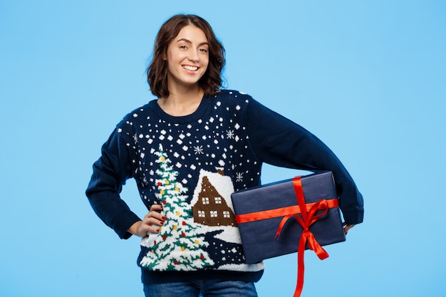 Young beautiful brunette girl in cosy knitted sweater smiling holding gift box over blue wall