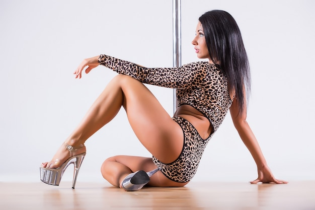 Young beautiful brunette girl doing pole dancing exercise