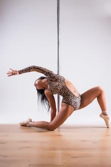 Молодая красивая брюнетка девушка делает упражнения для танцев на шесте