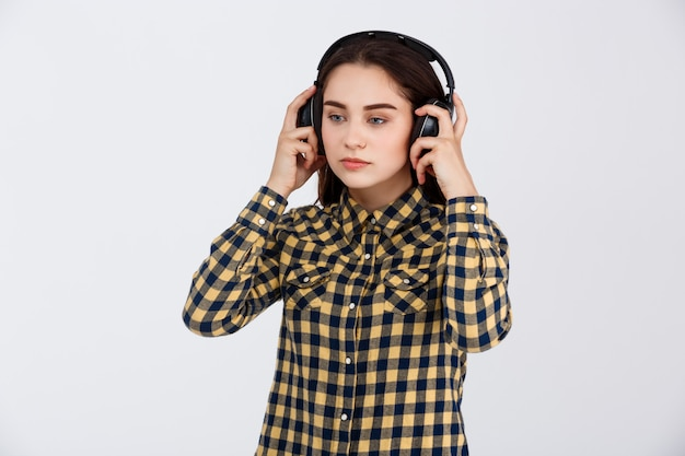 Young beautiful brunette girl dressed in plaid shirt listening music in headphones looking away over white wall