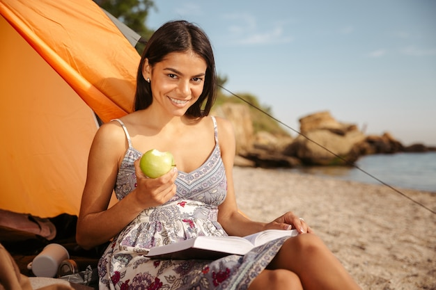 Young beautiful brunette girl eating apple and reading book while sitting at the beach camping