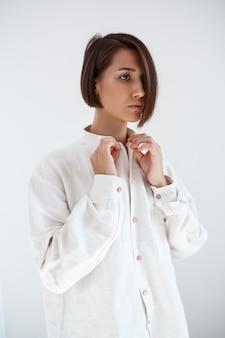 白い壁にシャツを締める若い美しいブルネットの少女