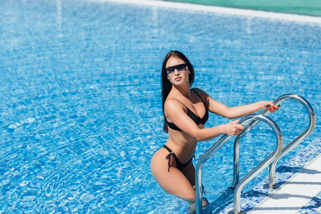 Young beautiful brunette girl fitness model in black swimsuit poses in the pool in the water.