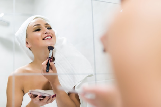 목욕 가운에 젊은 아름 다운 갈색 머리 소녀 거울을보고 화장을 적용