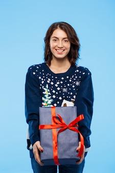 Молодая красивая брюнетка девушка в уютном вязаном свитере, улыбаясь, держа подарочную коробку над голубой стеной