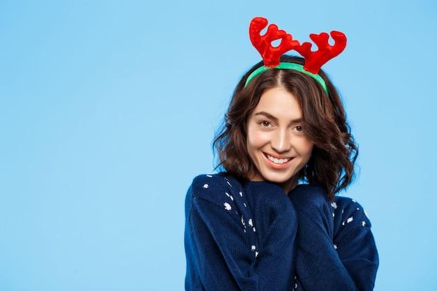 青い壁に笑みを浮かべてニットセーターとクリスマスのトナカイの枝角の若い美しいブルネットの少女