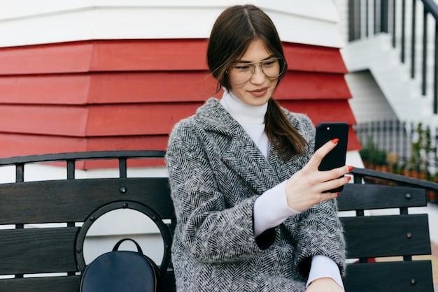 Молодая красивая брюнетка в стильном сером пальто сидит на скамейке на открытом воздухе и делает селфи