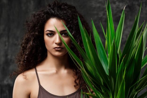 灰色の壁を越えて熱帯植物の若い美しいブルネットの少女