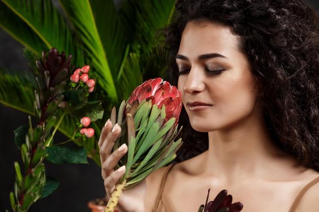 회색 벽에 열 대 식물에서 젊은 아름 다운 갈색 머리 소녀