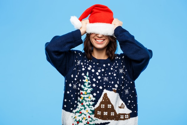 Young beautiful brunette girl in knitted sweater and christmas hat smiling  over blue wall