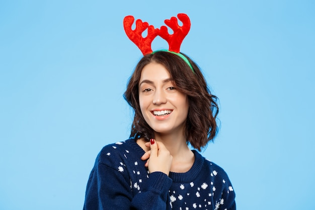 Young beautiful brunette girl in knitted sweater and christmas reindeer antlers smiling  over blue wall