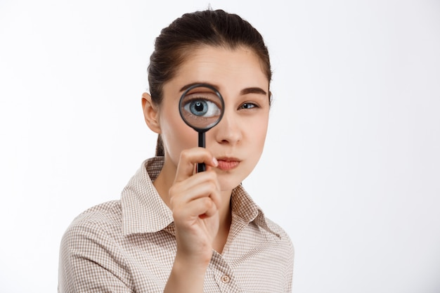 Young beautiful brunette girl looking with mistrust at camera through magnifier over white wall.