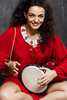 Young beautiful brunette girl playing drum over grey wall
