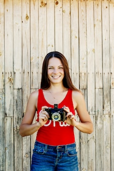 Young beautiful brunette girl in red shirt and jeans shorts posing with a camera on the rustic wooden background.