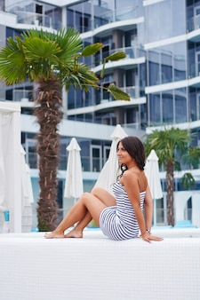 Young beautiful brunette girl resting under palm trees and hotel