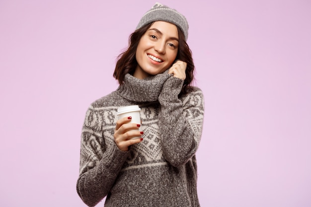 Young beautiful brunette girl smiling holding coffee over light wall