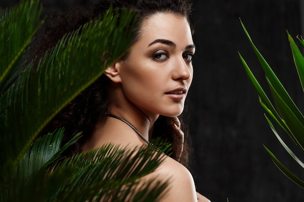 Young beautiful brunette girl in tropical plants over grey wall