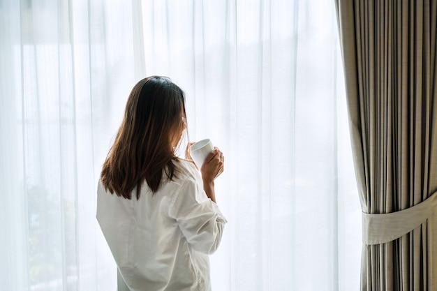Молодая красивая брюнетка с волосами женщина в белой рубашке пижаме пьет кофе, стоя у окна