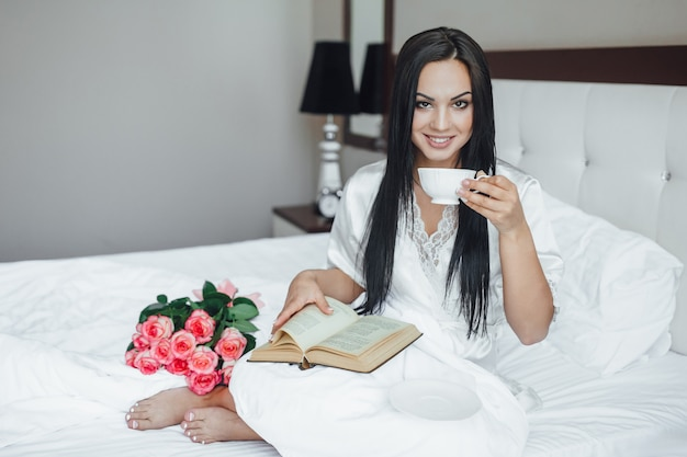 The young beautiful brunette happy girl sits in her bed with a bouquet of roses, drinks coffee and reads a book in the morning.