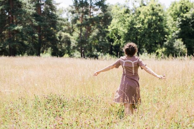 Молодая красивая брюнетка в платье в стиле кантри отдыхает на поле