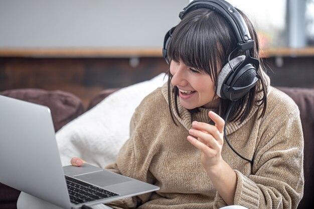 Молодая красивая брюнетка в наушниках улыбается в уютном свитере и смотрит на экран ноутбука. онлайн-обучение, удаленная работа, видеосвязь.
